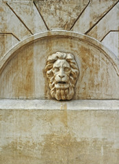 A lion's head on the wall of the old fountain