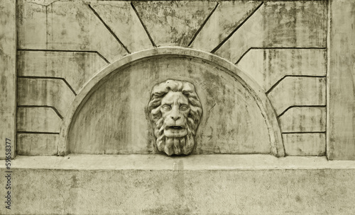 Sculpture of a lion's head in the arch of the old fountain