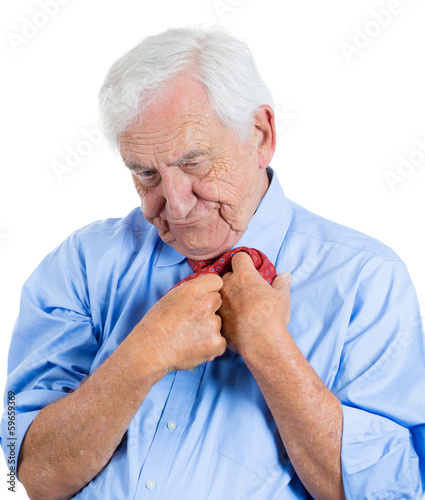 Stressed, anxious old man thinking, playing with his tie
