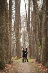 young lovers man and woman in the autumn forest
