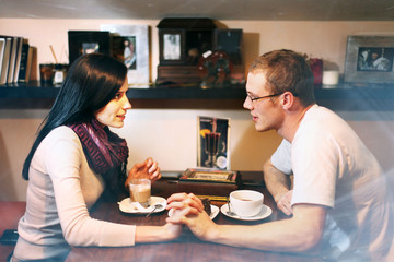 young lovers man and woman talking in the cafe