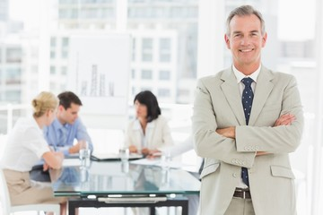 Happy businessman looking at camera while staff discuss behind h