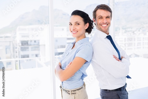 Smiling young business couple with arms crossed
