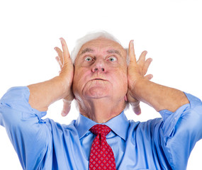 Stressed old man covering his ears from loud noise, headache