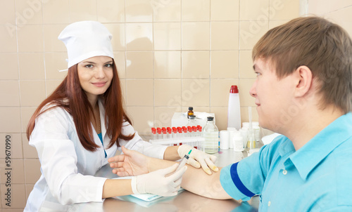 nurse prepares to make an intravenous injection