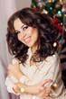 girl with curly dark hair near the Christmas tree