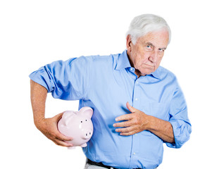 Senior man protecting piggy bank, possessive of savings