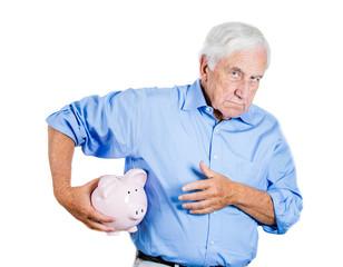 Senior man protecting piggy bank, possessive of savings