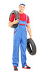 Full length portrait of a male mechanic holding a vehicle tires