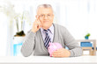Senior gentleman posing on a table with piggy bank