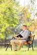 Senior man with hat seated on a wooden bench reading a book