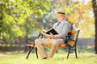 Senior man with hat sitting on a bench and reading a novel, in a