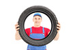 Smiling male worker holding a vehicle tire and looking at camera