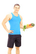 Young male athlete holding a dish full of fresh vegetables