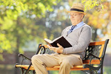 Senior man with hat sitting on bench and reading a book outside