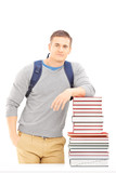 Smiling male student with school bag posing on a pile of books