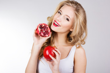 Portrait of young beautiful woman with pomegranates