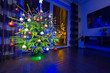 Christmas tree with decorations in the dark living room