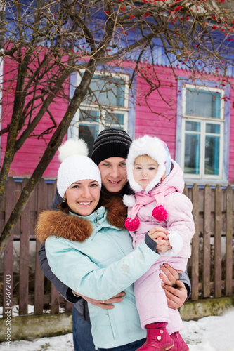 Beautiful family in warm clothes standing  of his house in winte