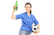Happy female fan holding a beer bottle and soccerball
