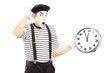 Male mime holding a clock and gesturing late