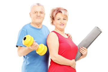 Mature man and woman posing with dumbbell and mat