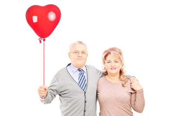 Middle aged couple in hug holding a red heart balloon
