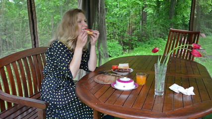blond woman in spotted dress eat sandwich for breakfast in bower
