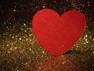 glitter background with red paper heart