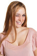 Frau mit langen blonden Haaren zwinkert zur Kamera
