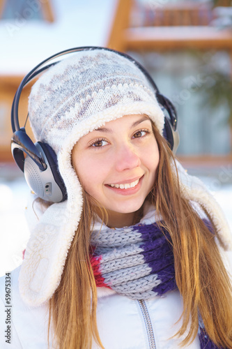 Outdoors on a winter day. Woman listening music.