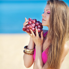 Portrait of beautiful woman with grapes in hands in summer outdo