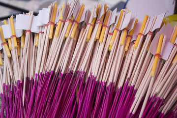 Incense sticks with candle and gold sheet in paper cover