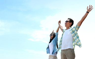 Asian Young couple standing and raised their hands to the sky