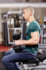 Athletic man working with heavy dumbbells