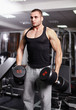 Athletic man holding heavy dumbbells