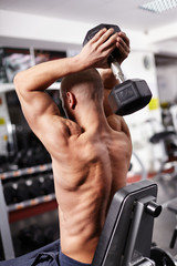 Athletic man working with heavy dumbbell
