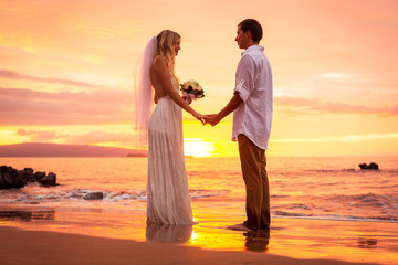 Just married couple on tropical beach at sunset