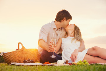 Attractive couple kissing on romantic picnic