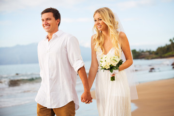 Just married couple walking on the beach at sunset