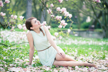 Beautiful young woman sitting under a magnolia tree