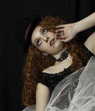 Beautiful young woman wearing top hat and crinoline