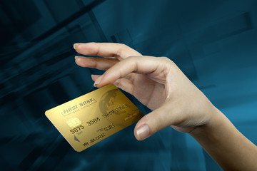 a woman's hand holding a gold credit card