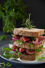 Grain bread sandwich with roast beef, onion and arugula.