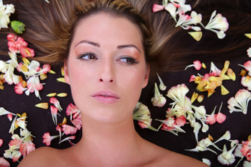 Junge hübsche Frau, liegend mit Blumen