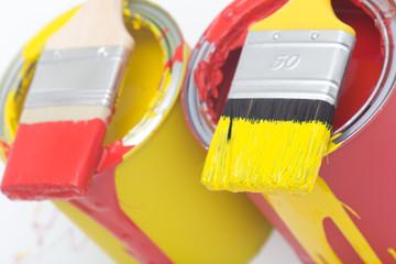 Roter und gelber Farbpinsel auf Farbdosen