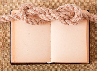 Knot sea and old book on background of the old fabric