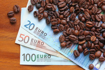 Coffee beans on top of Euro banknotes money
