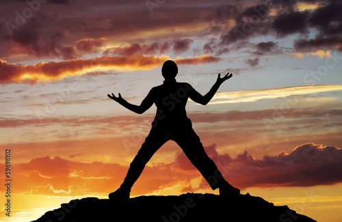 Silhouette of man on sunset sky background