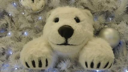 Decorated and lighted Christmas tree. Polar teddy bear